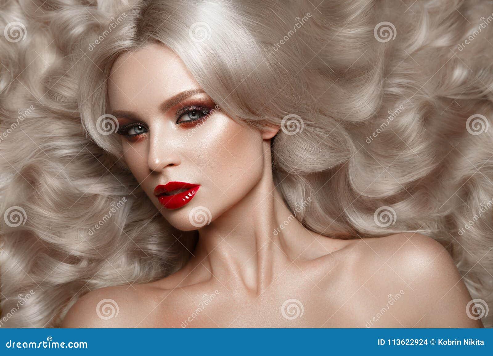美丽的金发碧眼的女人以与卷毛、自然构成和红色嘴唇的好莱坞方式 秀丽表面和头发