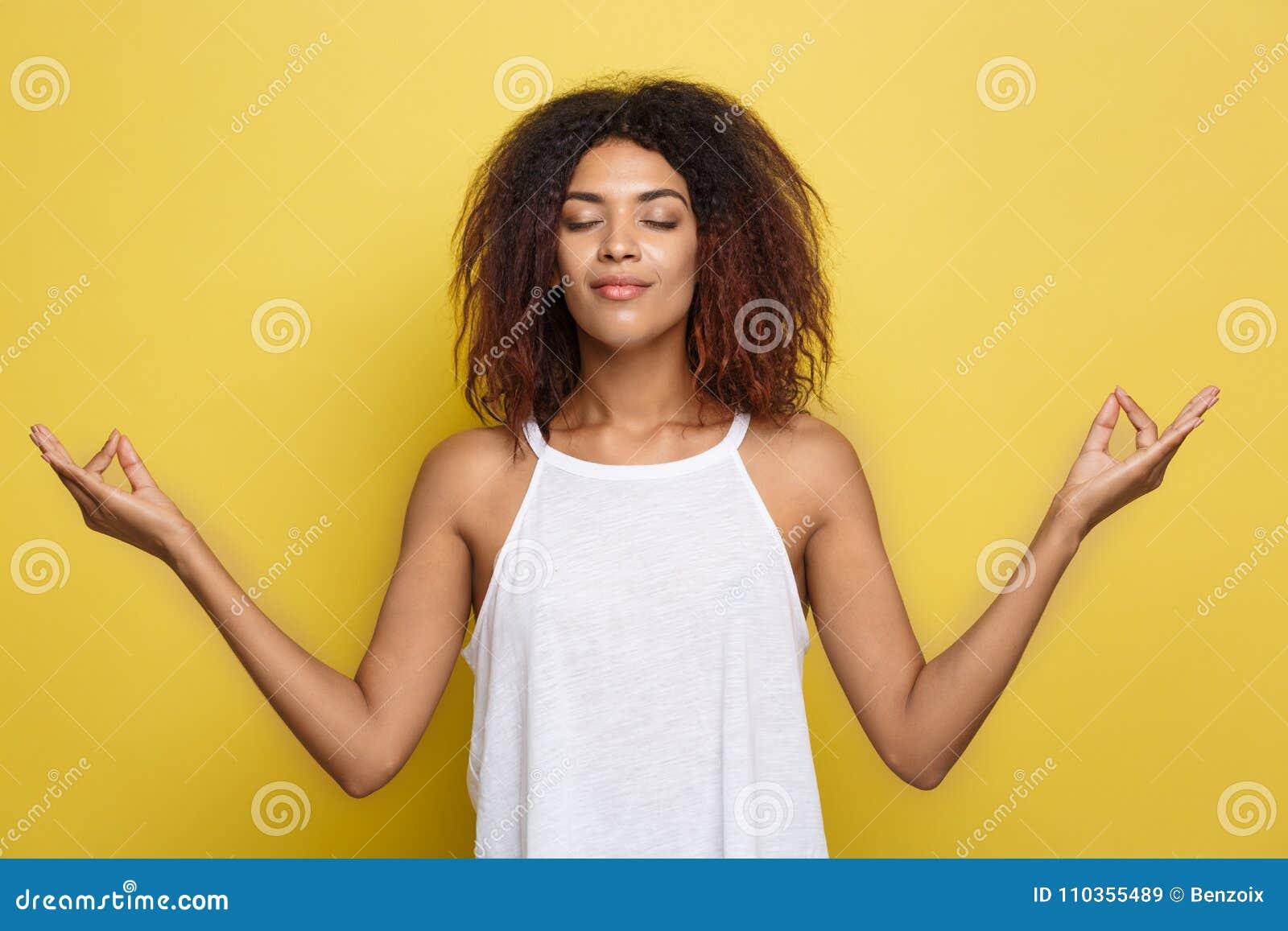 美丽的镇静年轻非裔美国人的黑人女性画象有蓬松卷发发型实践的瑜伽的户内,思考