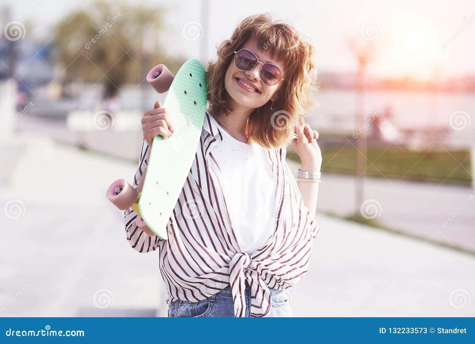 美丽的青少年的女性溜冰者坐舷梯在冰鞋公园 夏天都市活动的概念