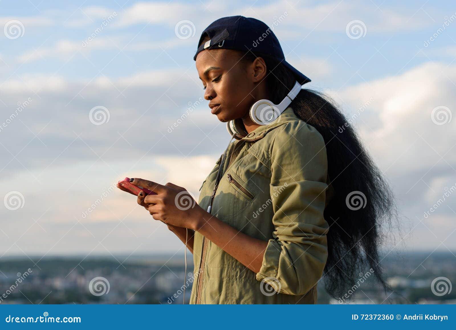 美丽的非裔美国人的女孩听到音乐并且享用 被弄脏的城市背景的微笑的年轻黑人妇女