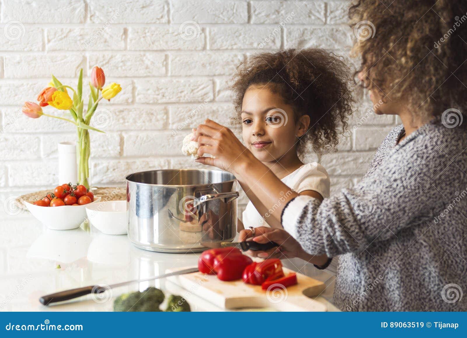 美丽的非裔美国人的妇女和她女儿烹调