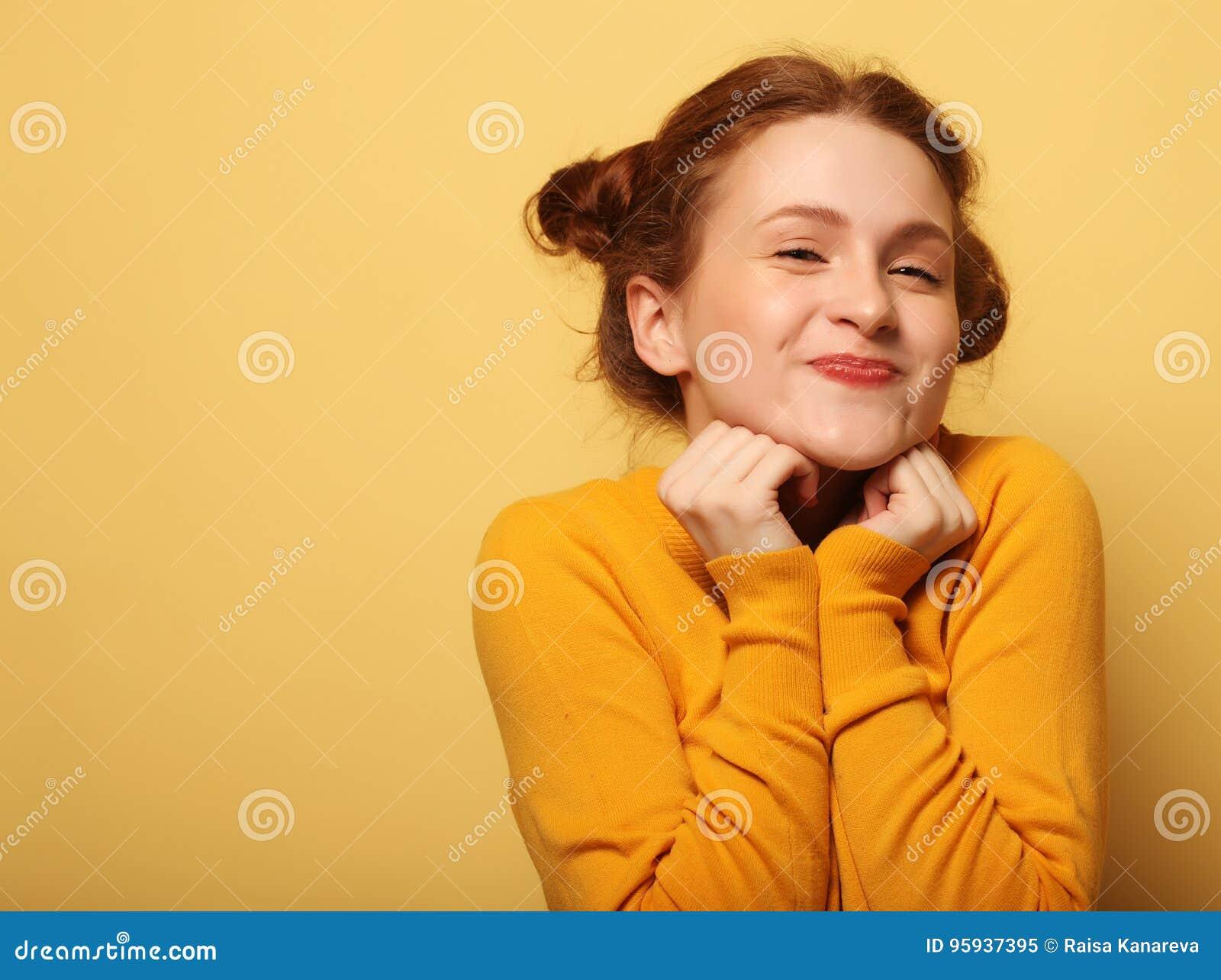 美丽的年轻人使在黄色背景的redhair妇女惊奇