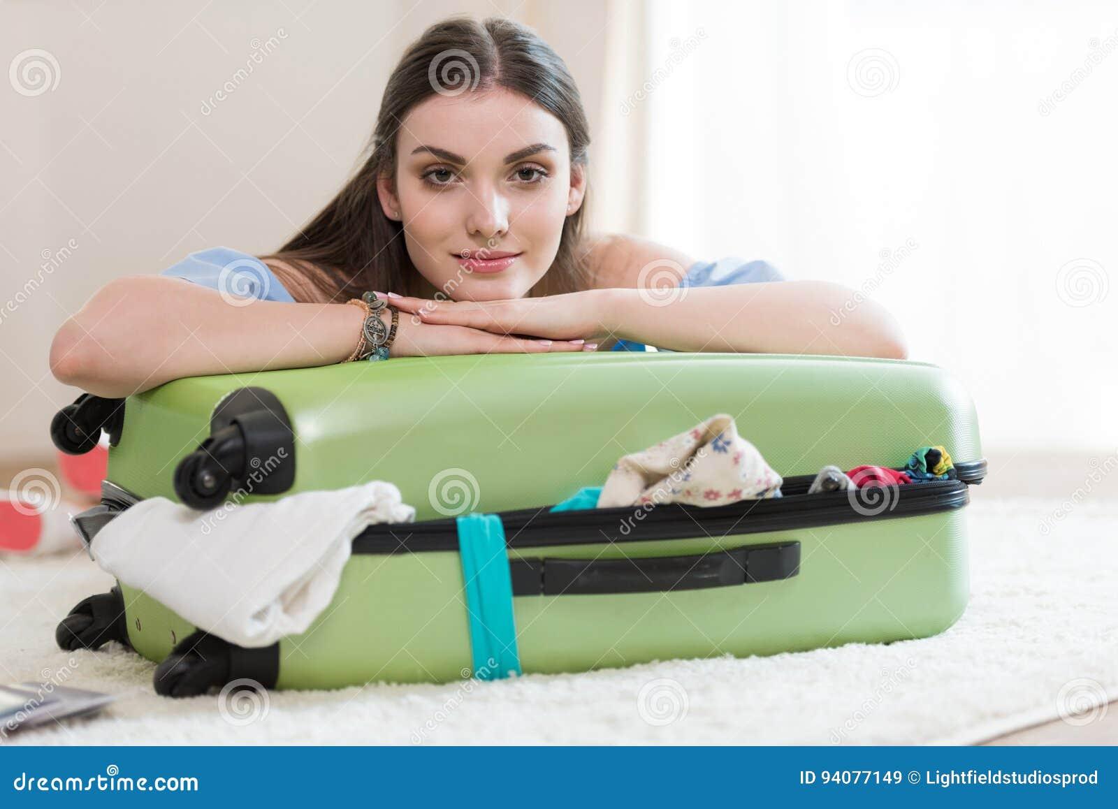 美丽的年轻深色的妇女包装手提箱和看照相机
