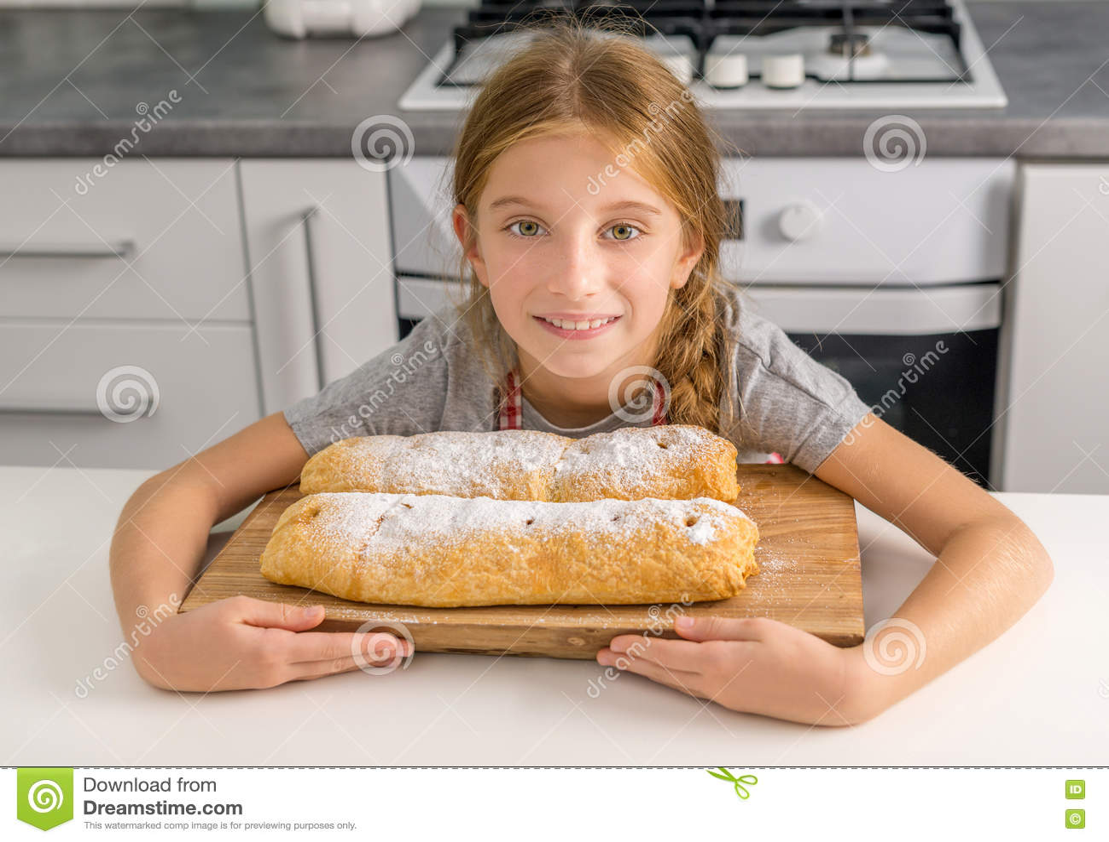 美丽的litte女孩用在桌上的被烘烤的苹果果馅奶酪卷