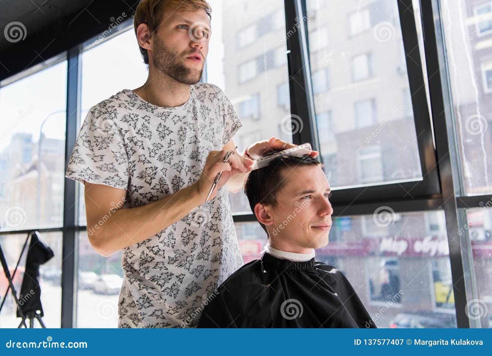 美发师做有英俊的满意的客户梳子的头发专业理发沙龙的
