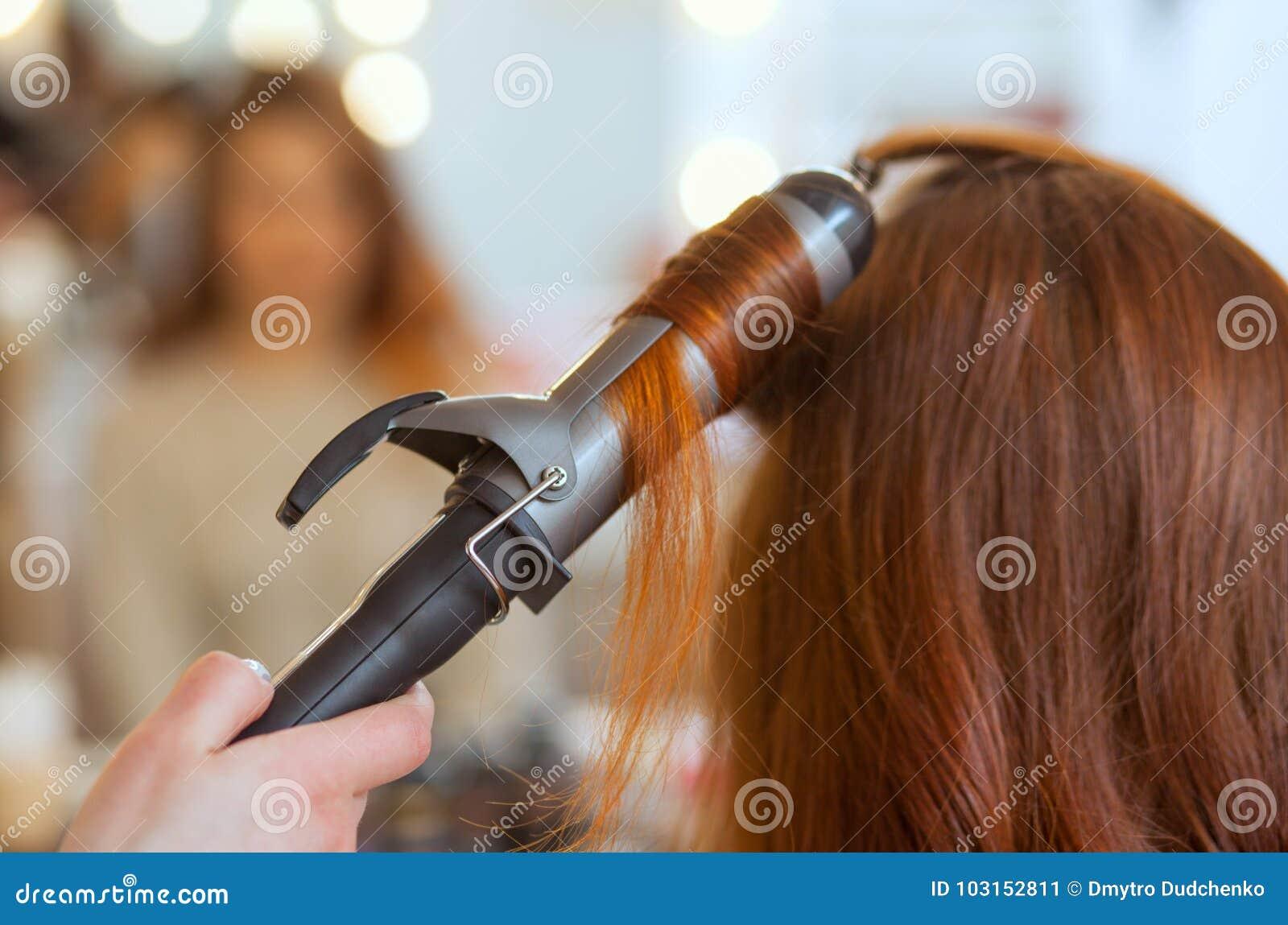 美发师做有长的红色头发的发型女孩在美容院