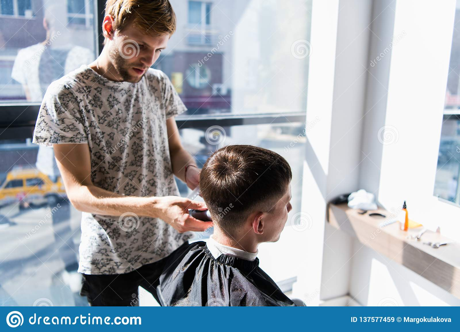 美发师在一把电剃刀和一把梳子帮助下成水平理发在理发店