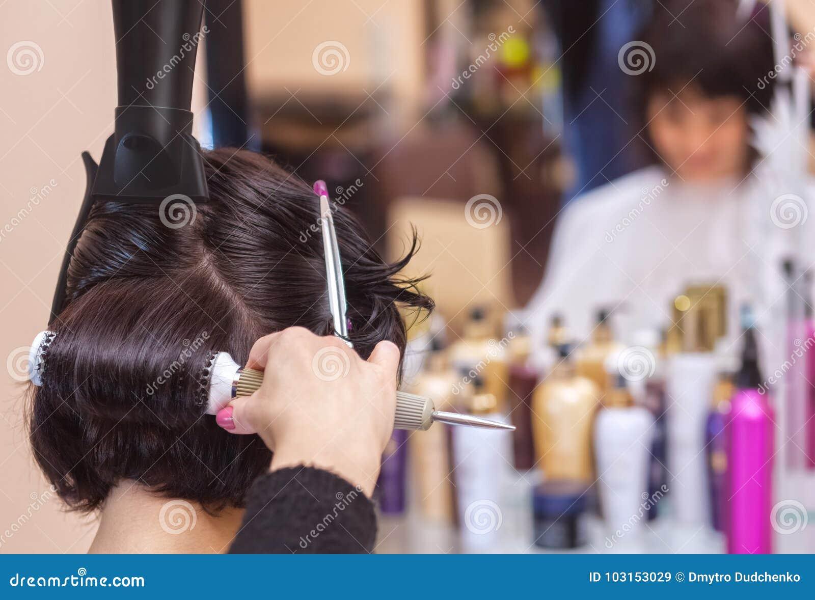 美发师烘干她的头发一个深色的女孩