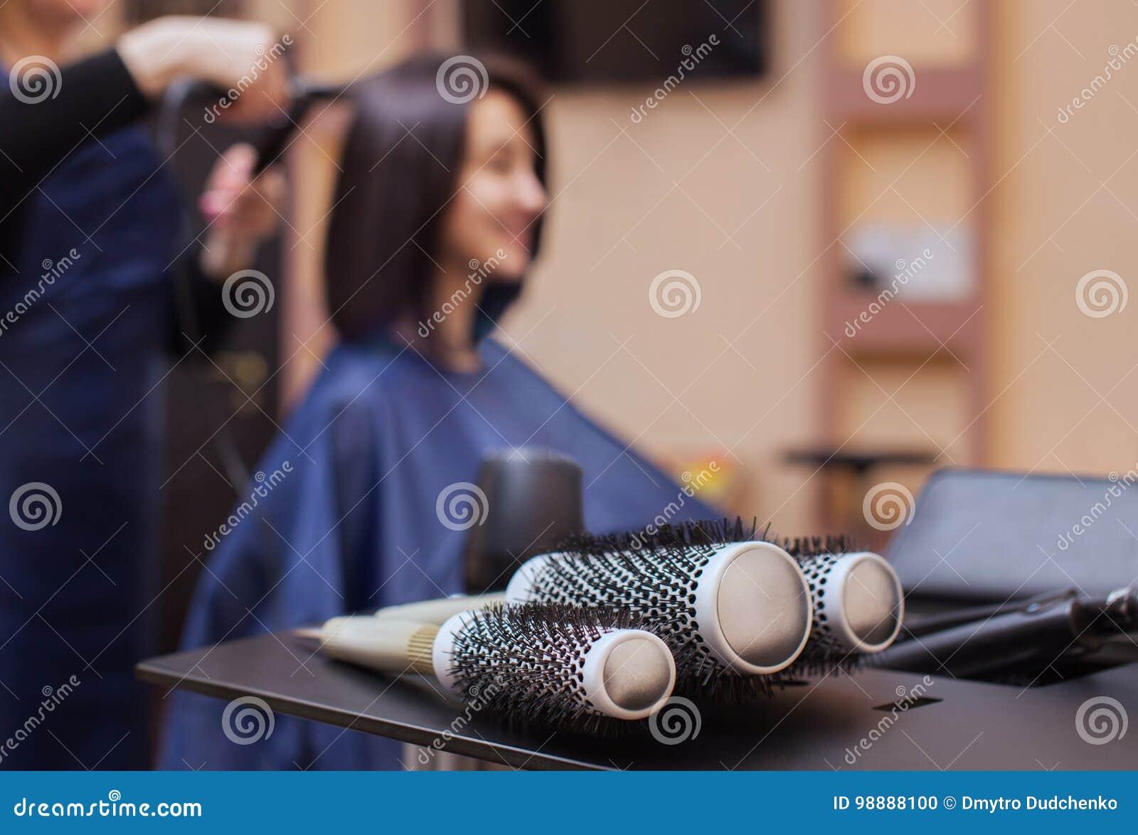 美发师烘干她的头发美容院的一个深色的女孩
