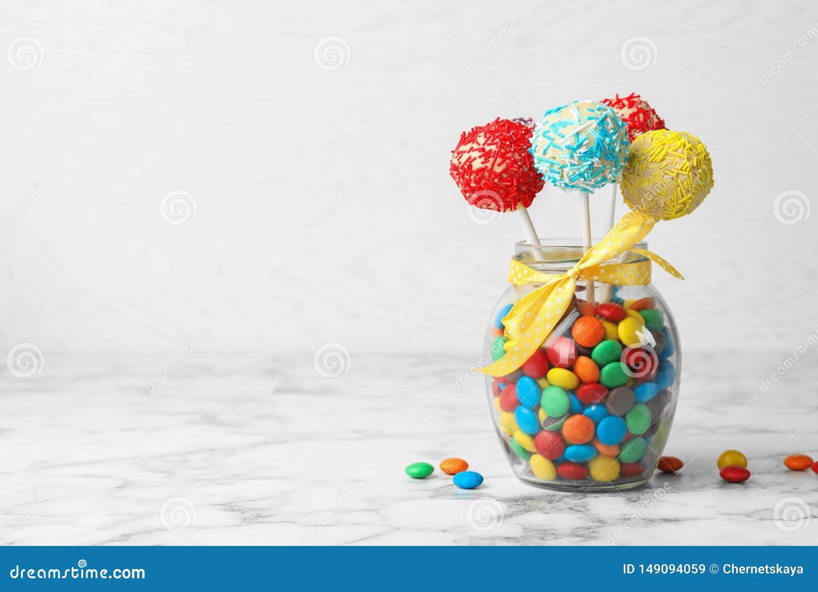美味的明亮的蛋糕在玻璃瓶子充分流行在桌上的糖果