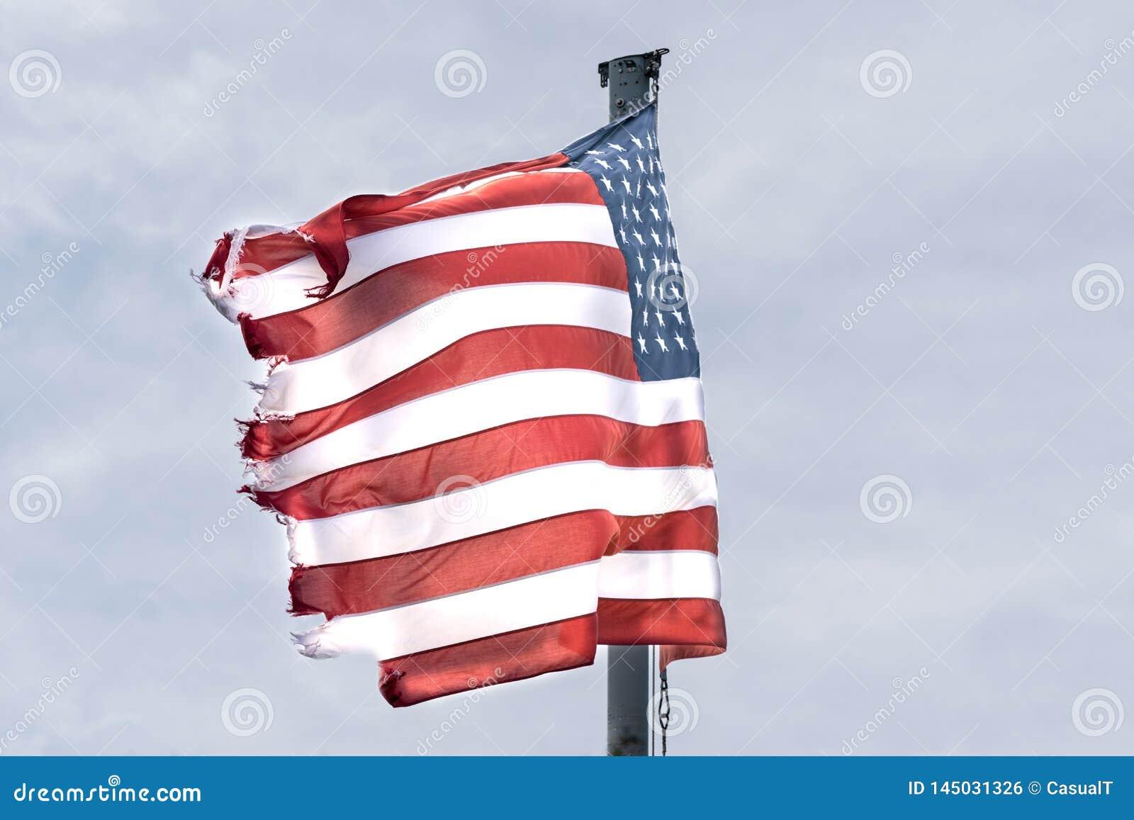 美国国旗,星&Stripes,被撕碎和磨损在边缘,吹在风在一灰色和阴沉的天,块