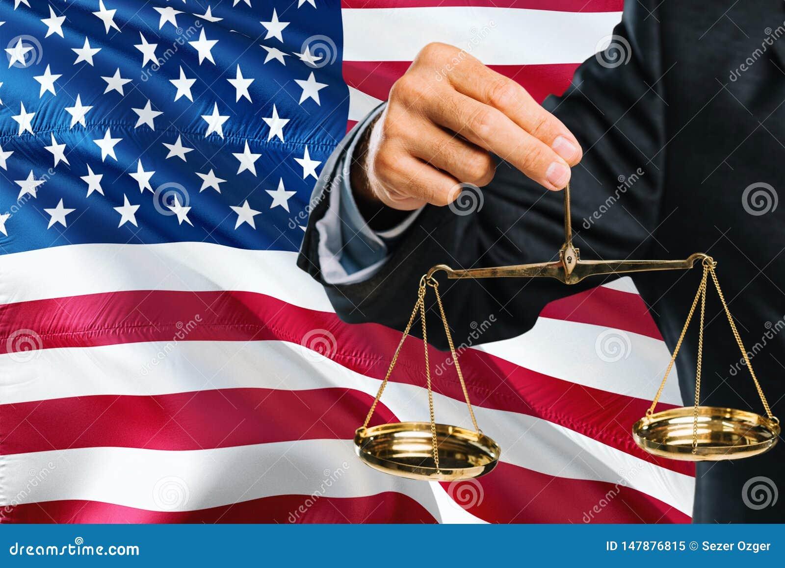 美国法官拿着正义金黄标度有美国挥动的旗子背景 平等题材和法律概念