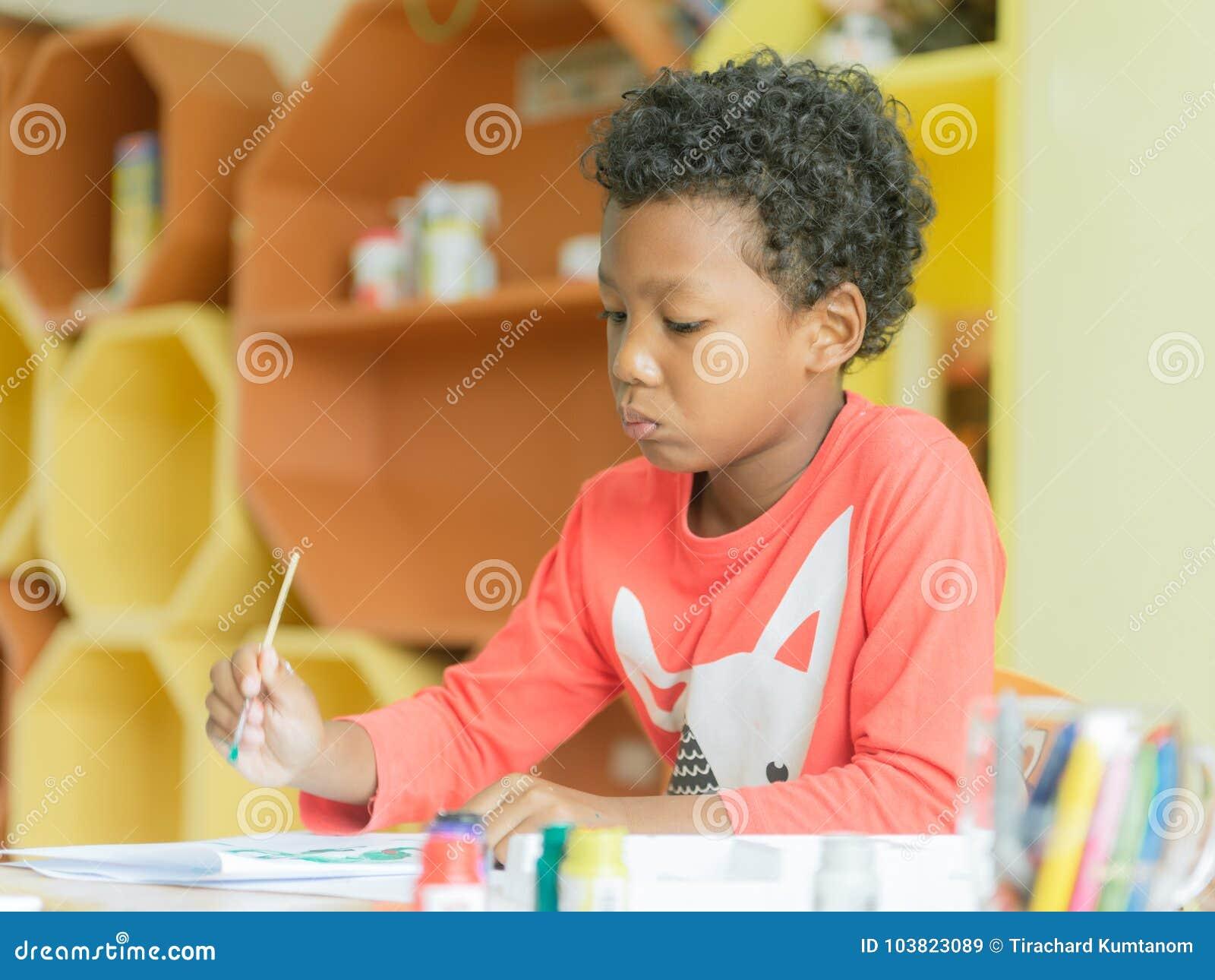 美国男孩做在家佩带了在幼儿园教室、学龄前图书馆和孩子教育概念的绘画颜色铅笔