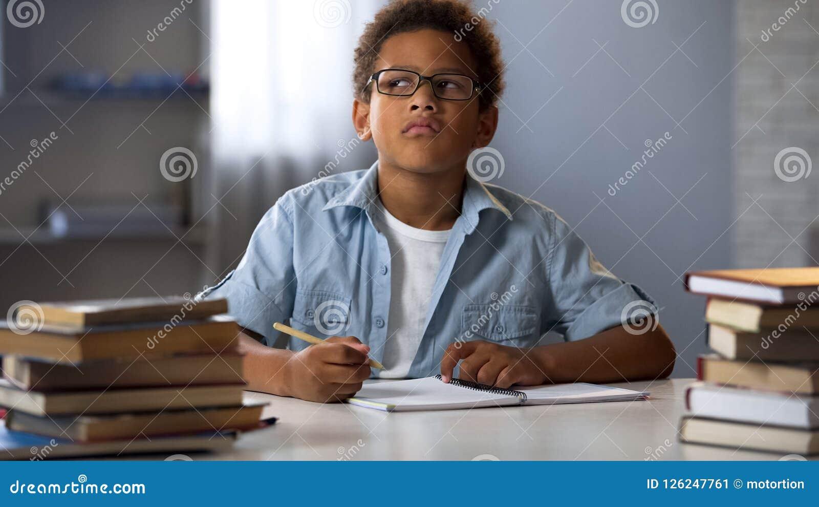 美国黑人的男孩认为在学校杂文的,做家庭作业,教育的聪明的孩子