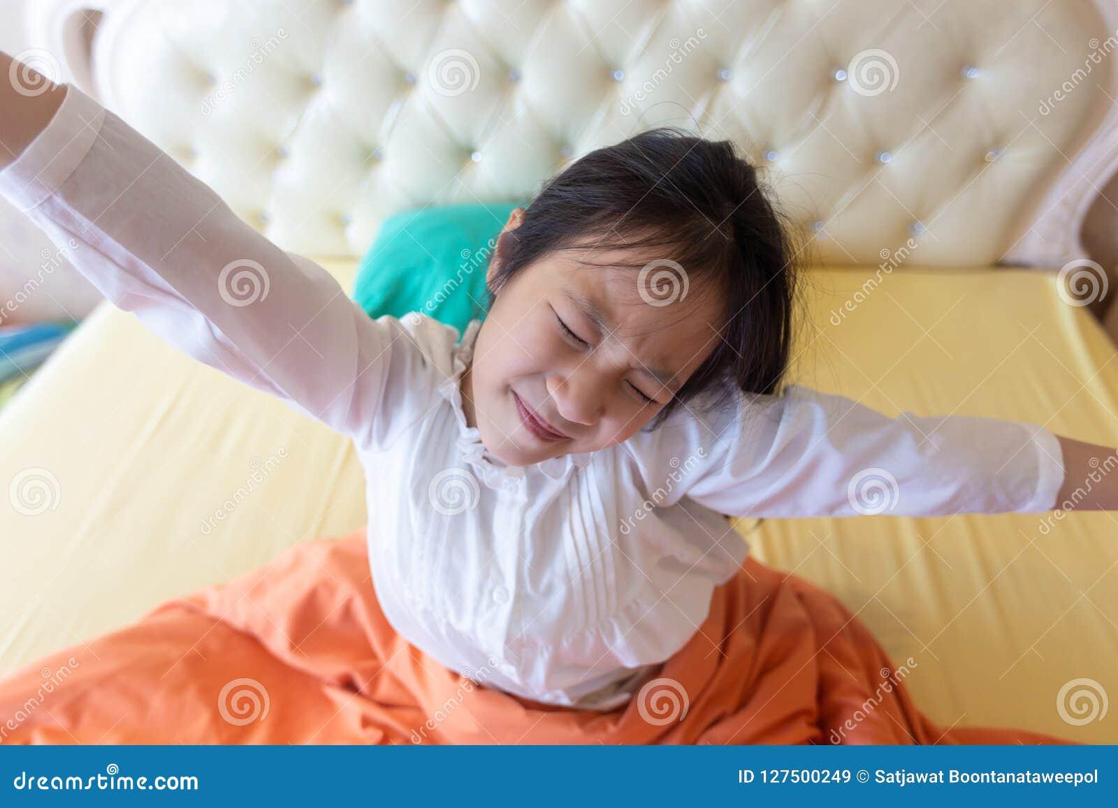 美女醒在她的床上的,舒展亚裔的女孩微笑和,健康,生活方式概念