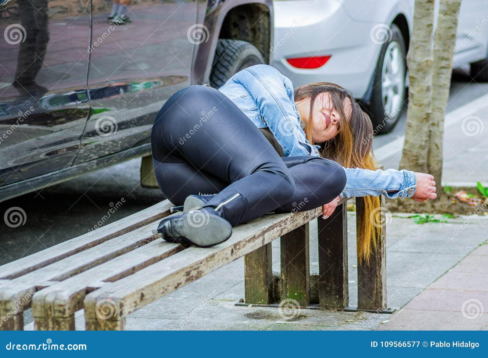 美好少妇穿着体面睡觉在一把公开椅子在公园,上瘾者概念