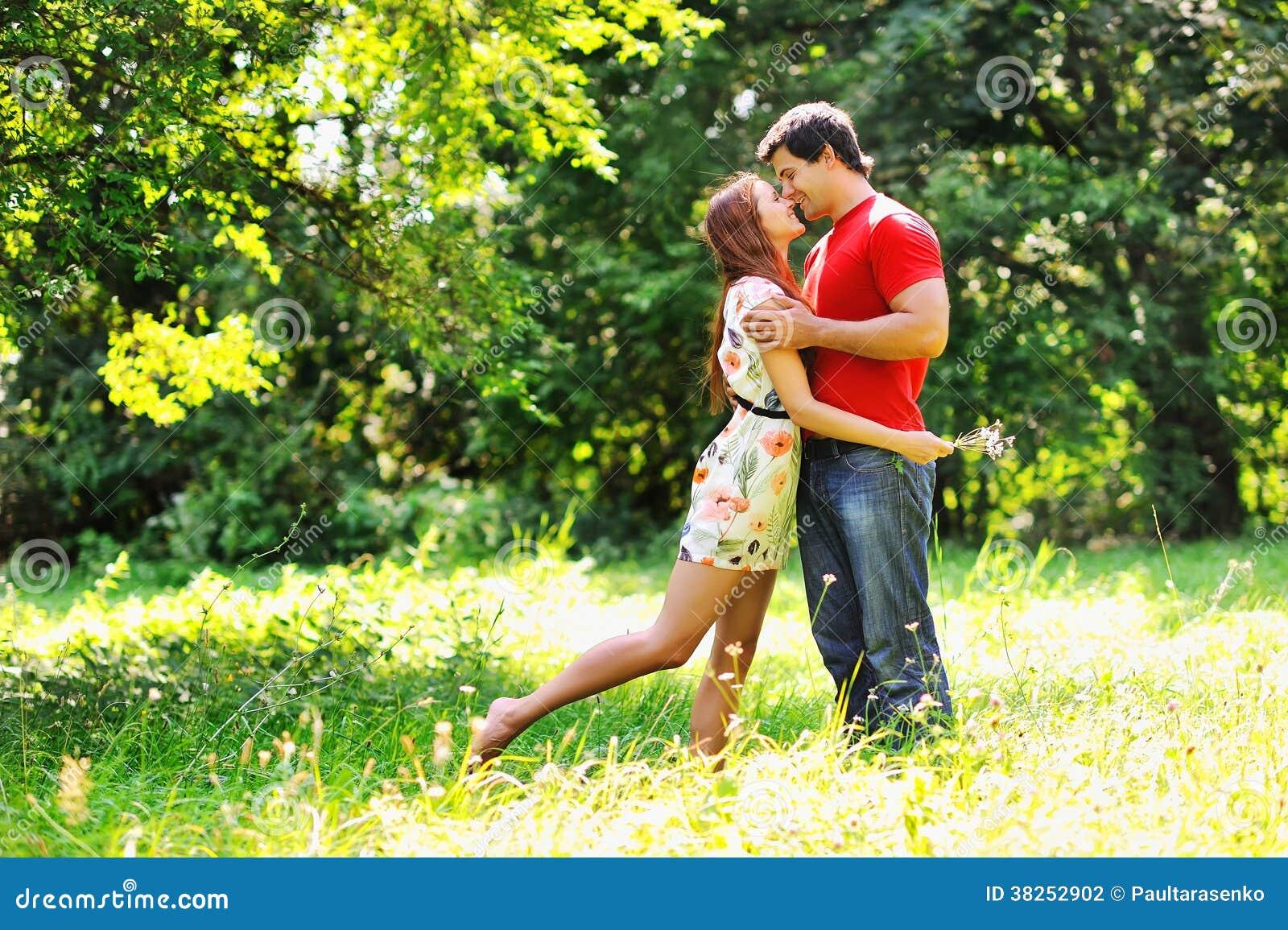 年轻美好的夫妇。笑和亲吻。夏天绿色公园