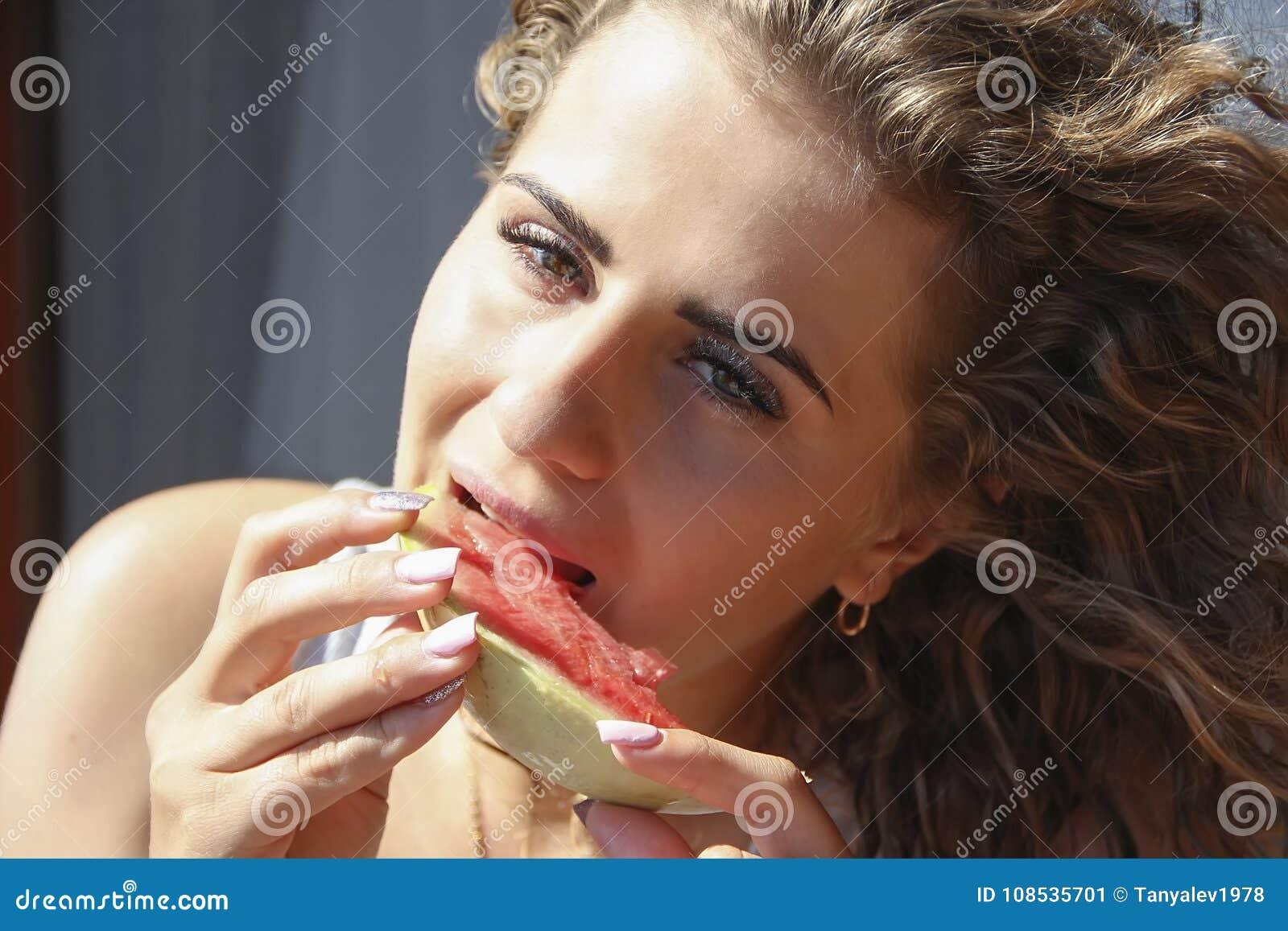 美好的妇女吃西瓜卷发夏天