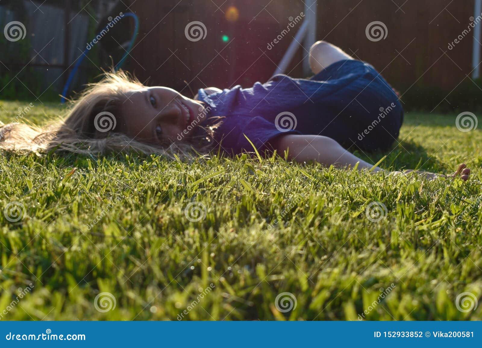 美好的少女关闭在绿草在夏天 女孩的微笑的童颜