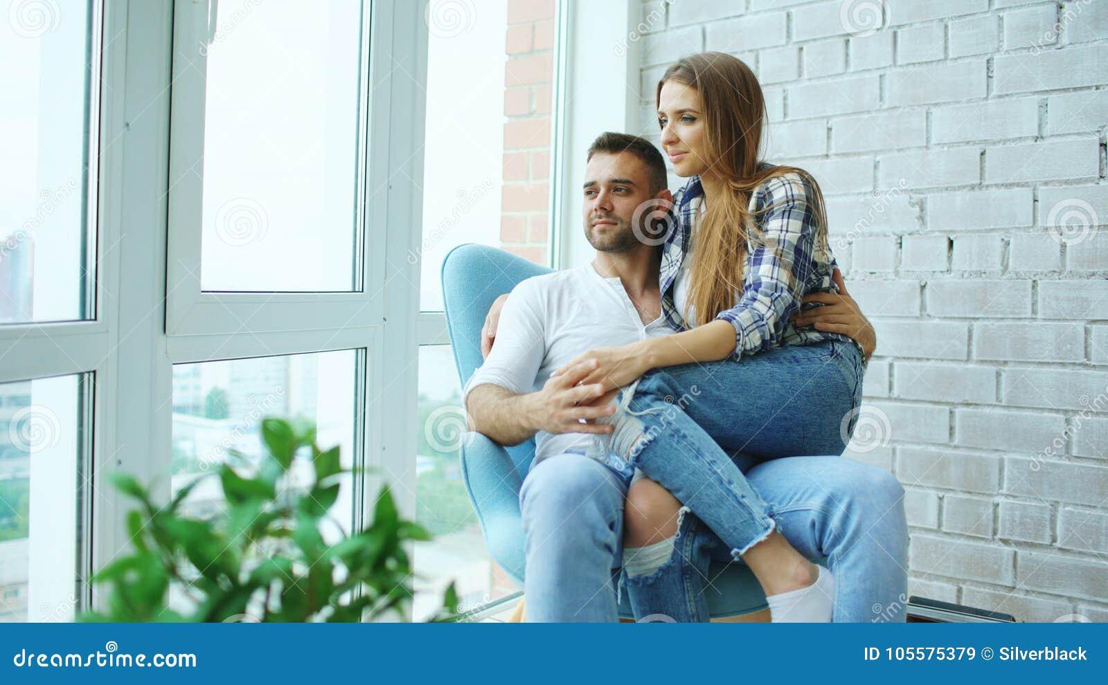 美好的年轻夫妇放松坐椅子和享受从新的顶楼公寓阳台的看法