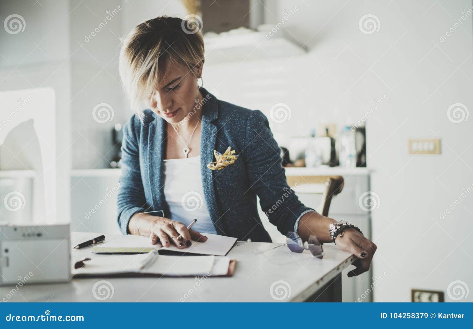 美好的年轻女实业家文字某事在笔记本,当坐扶手椅子在客厅时 迷人的女性