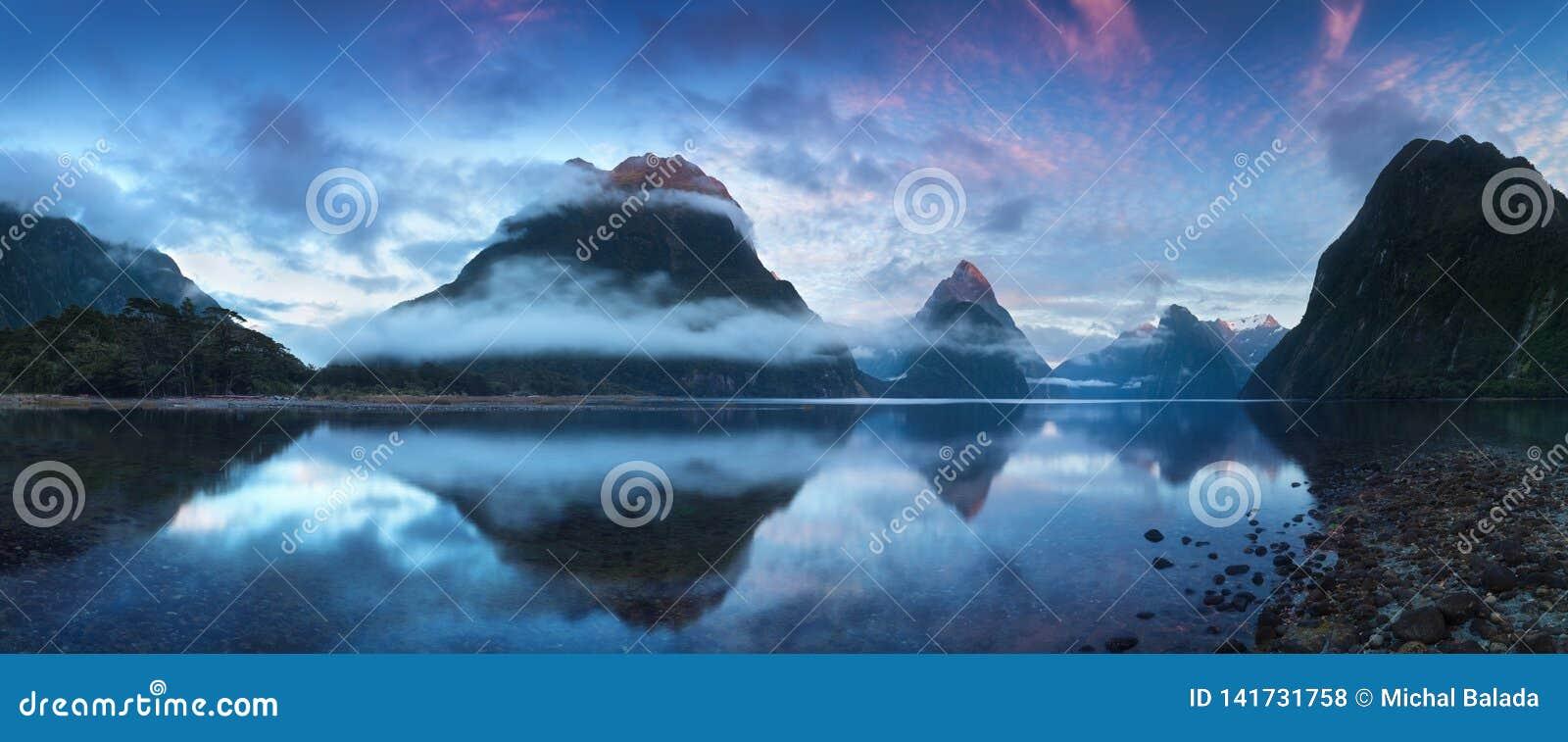 美好的日出在米尔福德峡湾,新西兰 - 主教峰顶是米尔福德峡湾偶象地标在峡湾国家公园
