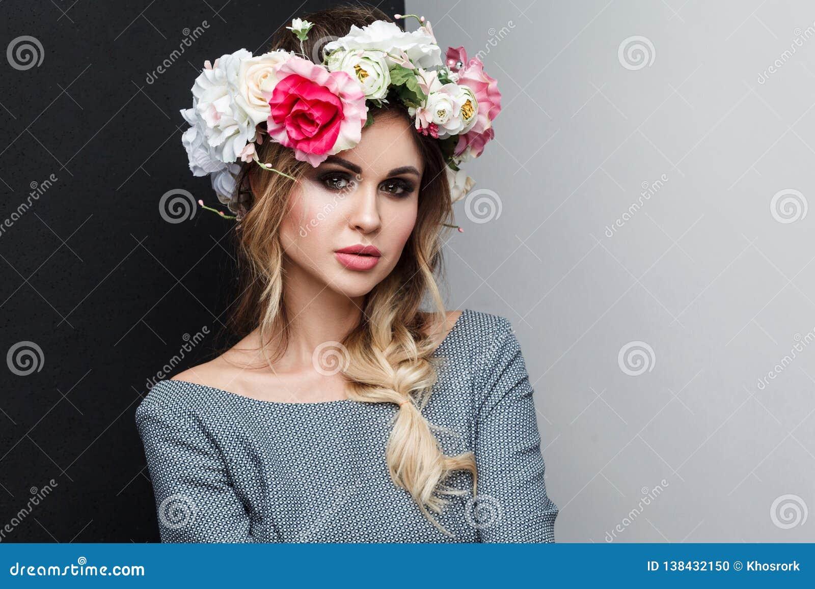 美好的有吸引力的时装模特儿特写镜头画象在灰色礼服的有构成、发型和顶头花的在她的头,看