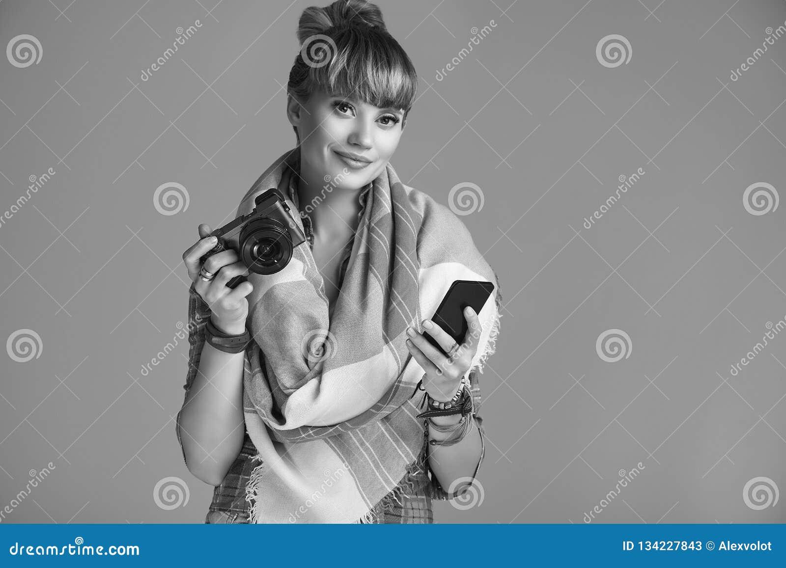 美好的有照相机和电话的魅力白肤金发的嬉皮妇女