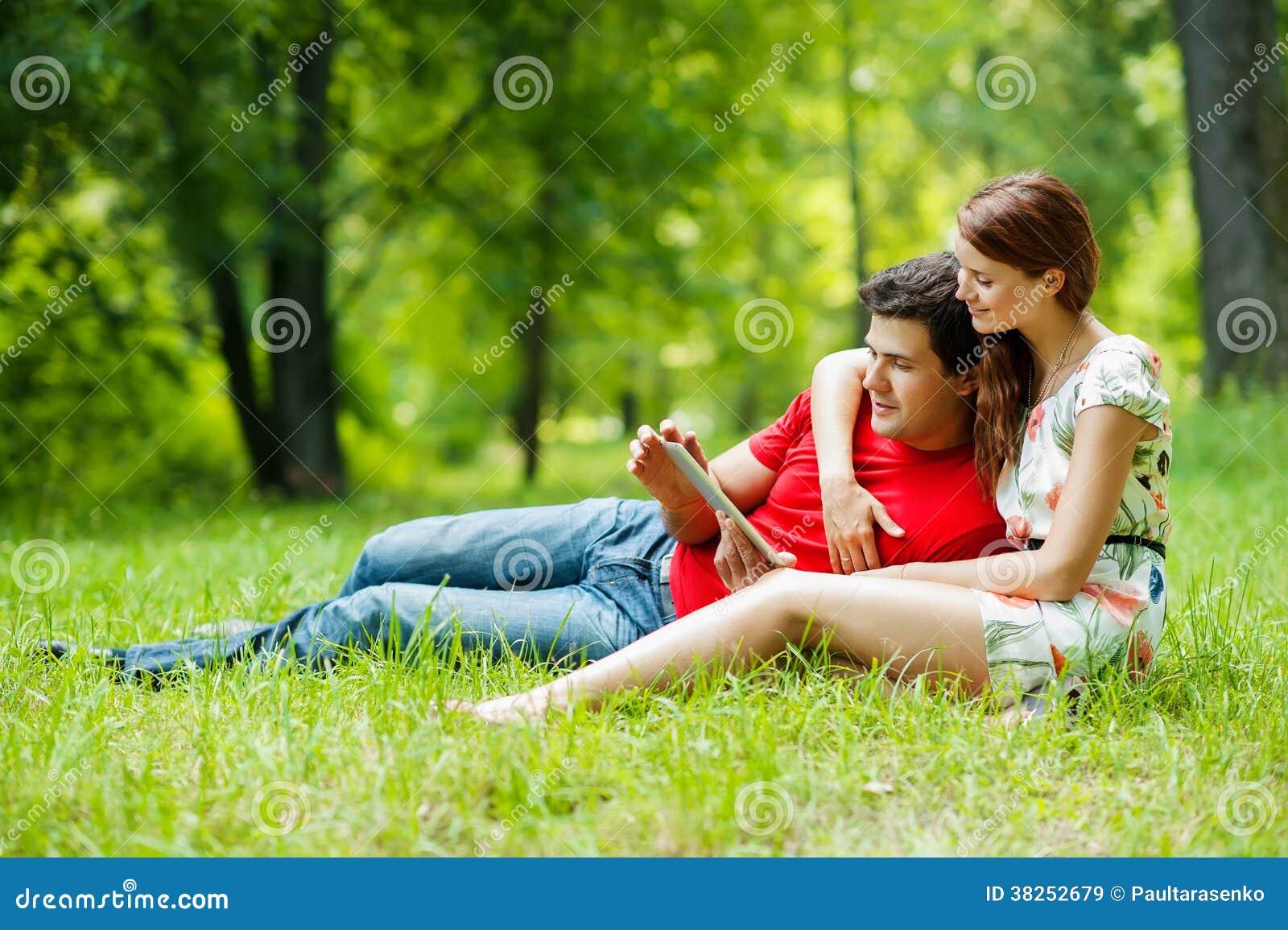 美好的浪漫加上片剂个人计算机在夏天绿化公园