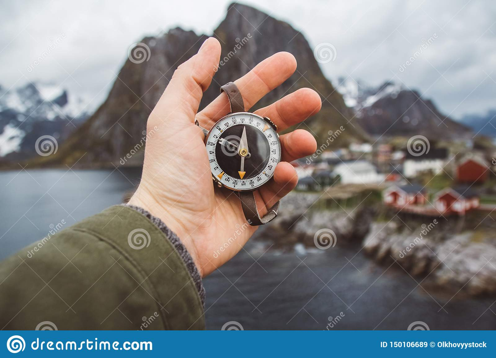 美好的男性手拿着一个磁性指南针以房子和山岩石为背景在海湾
