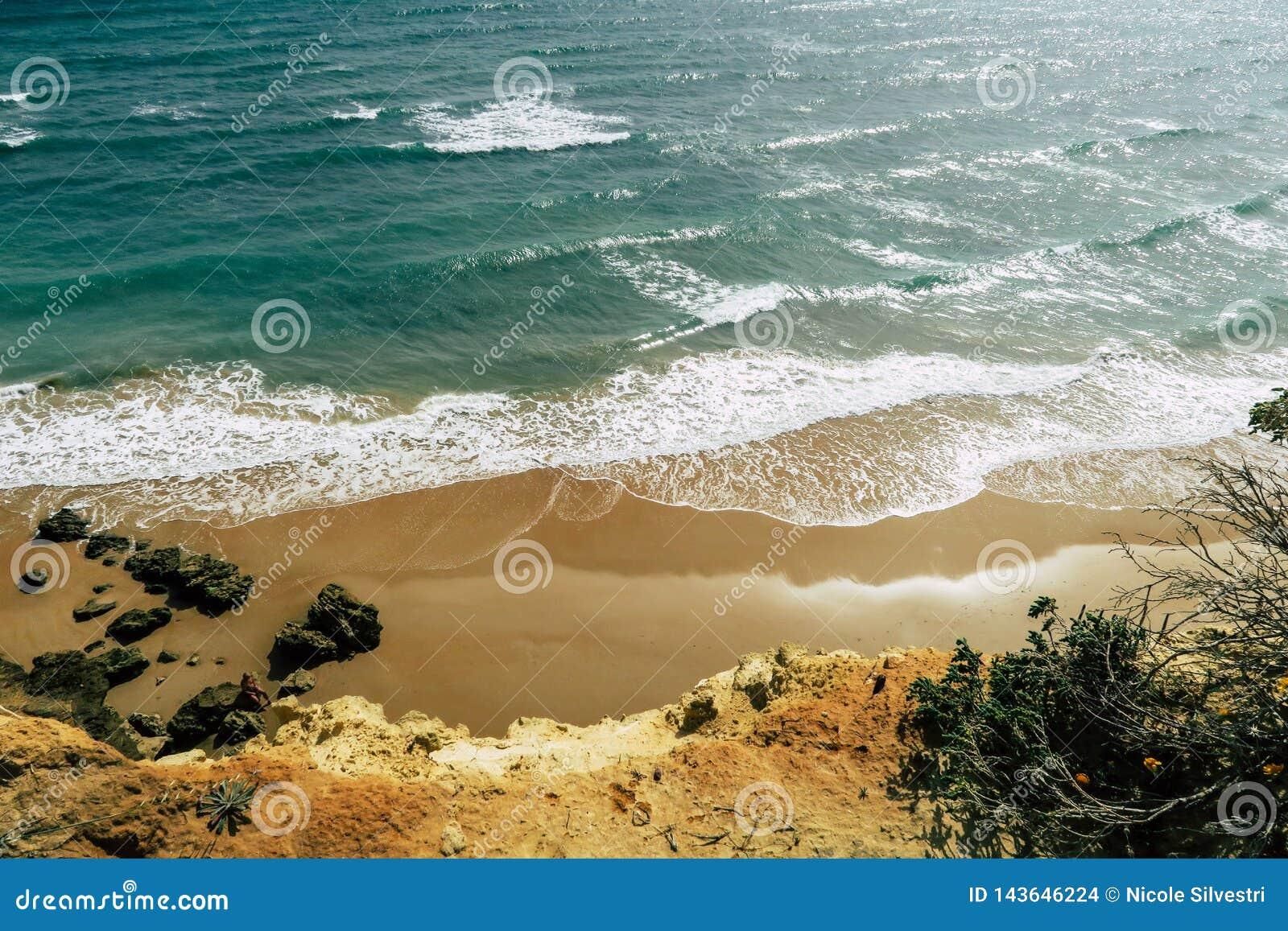 美好的西班牙海滩和海岸线与峭壁:海,与白色冠的波浪在日落期间