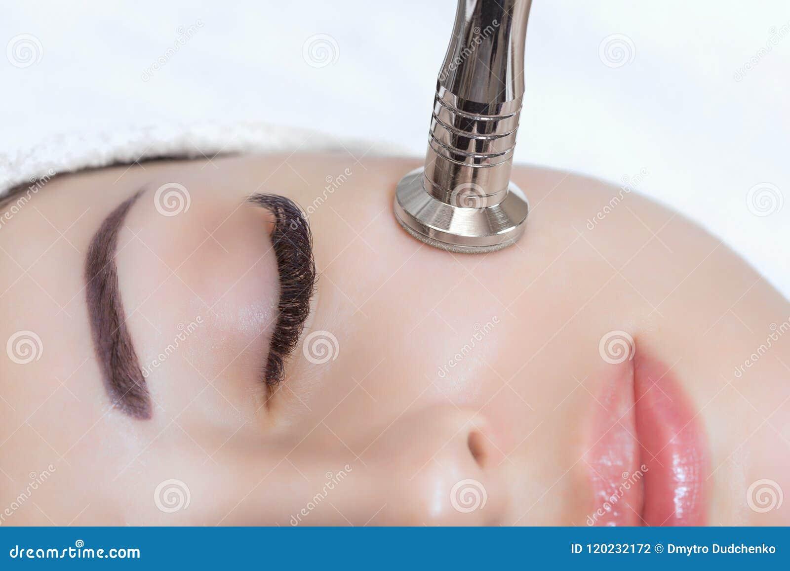 美容师做做法Microdermabrasion一个美丽,少妇的面部皮肤