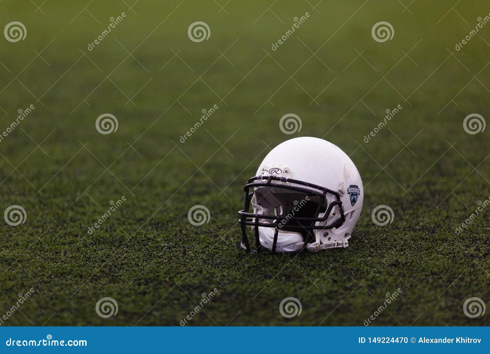 美式足球橄榄球比赛的防护白色盔甲在运动场的绿草说谎