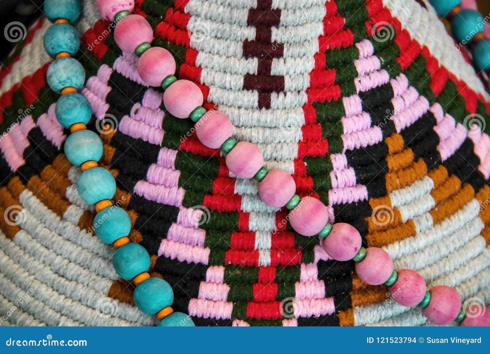 美洲印第安人装饰背景-桃红色和在一件五颜六色的纺织品装饰的绿松石小珠被编织设计特写镜头和浅焦点