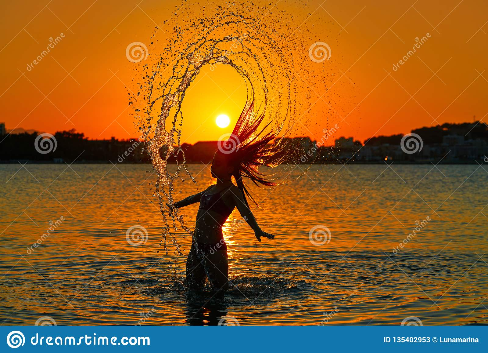 翻转头发轻碰的女孩在日落海滩