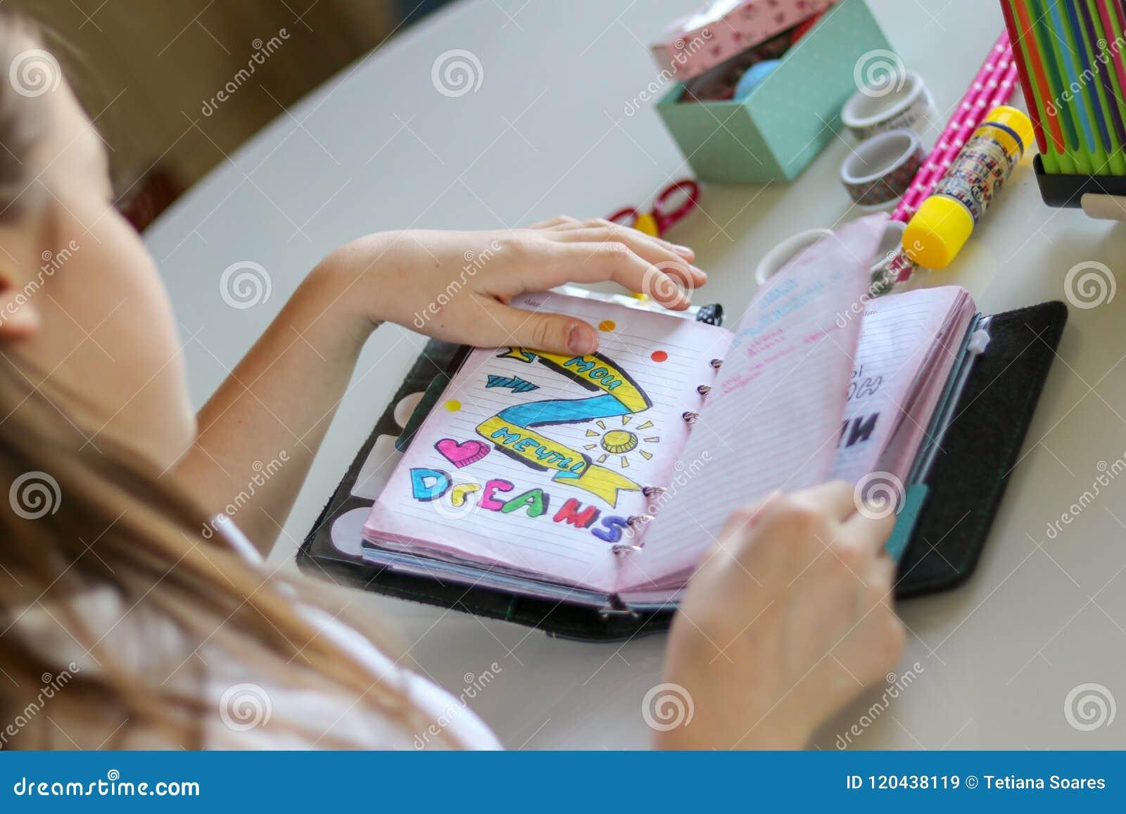 翻转通过她的日志的年轻青春期前的女孩写下她的梦想,签署我的梦想用俄语