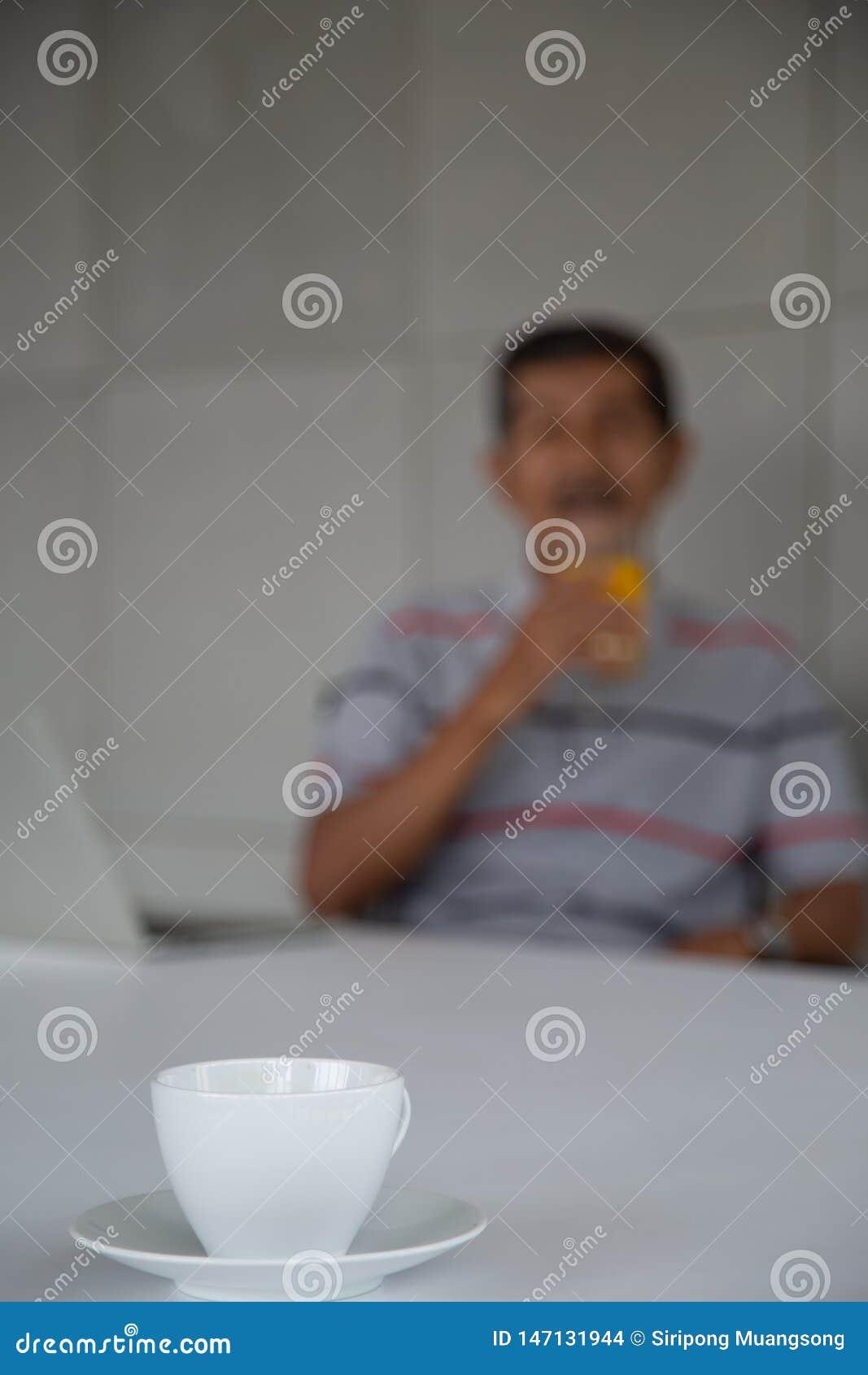老人健康的饮料橙汁过去在他的工作室