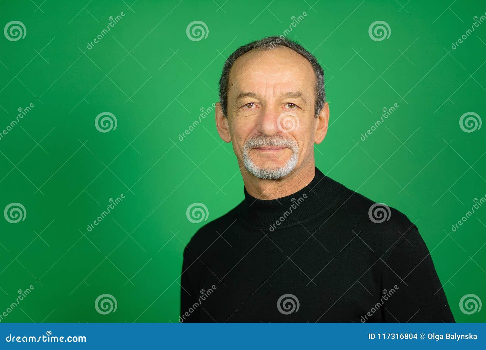 老人和在绿色背景的灰色头发的男性面孔演播室射击有被整理的胡子的
