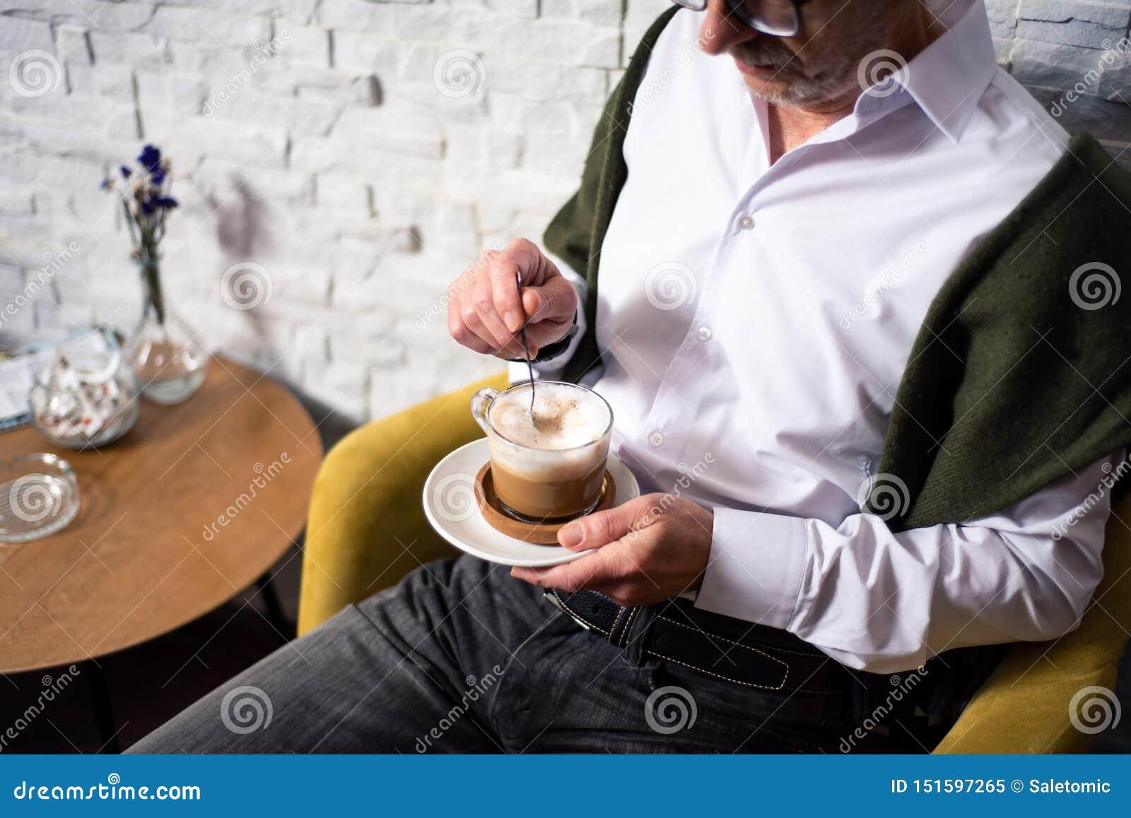 老人喝咖啡在酒吧
