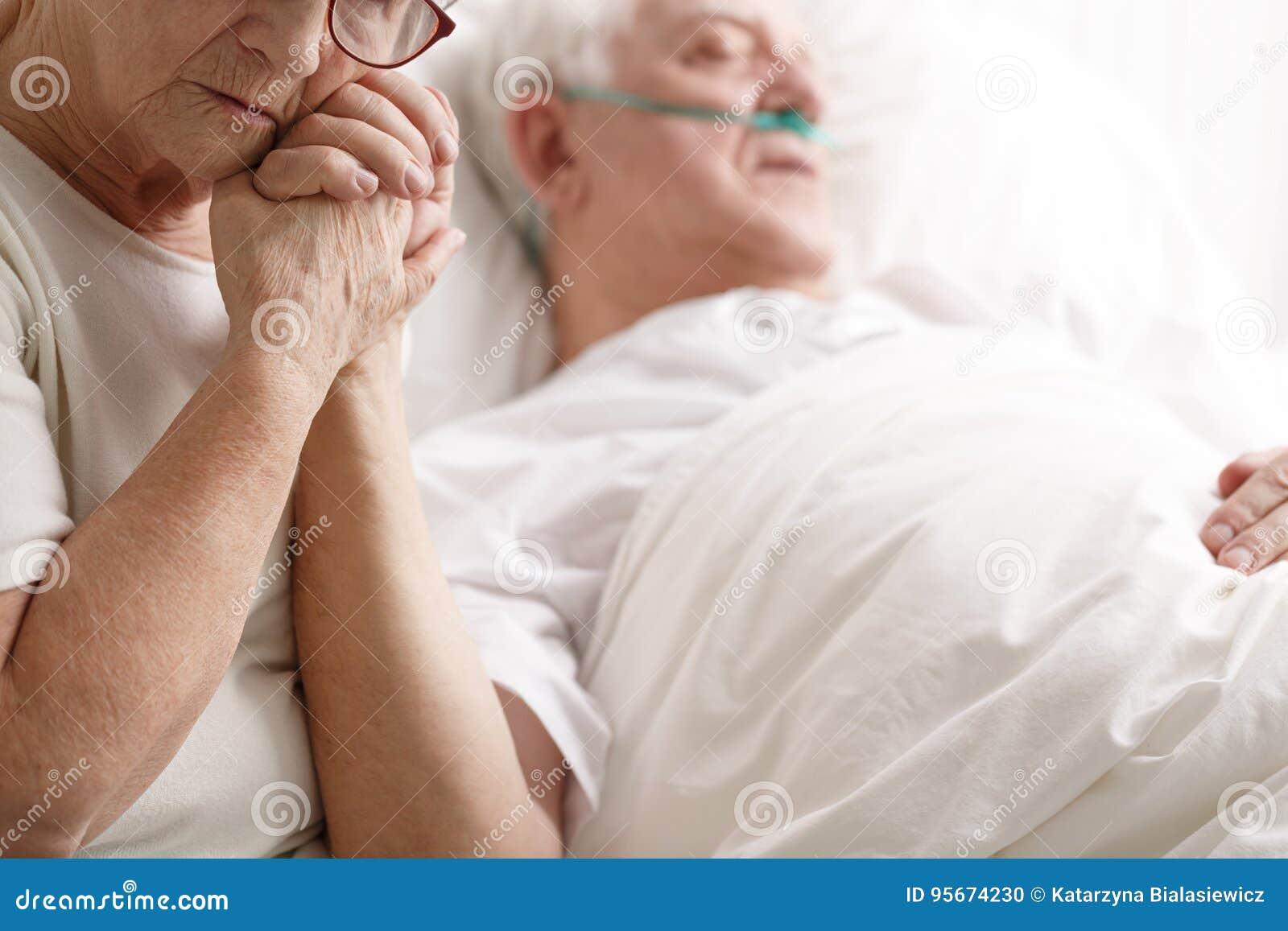老人在医院病床上和他的握他的手的妻子