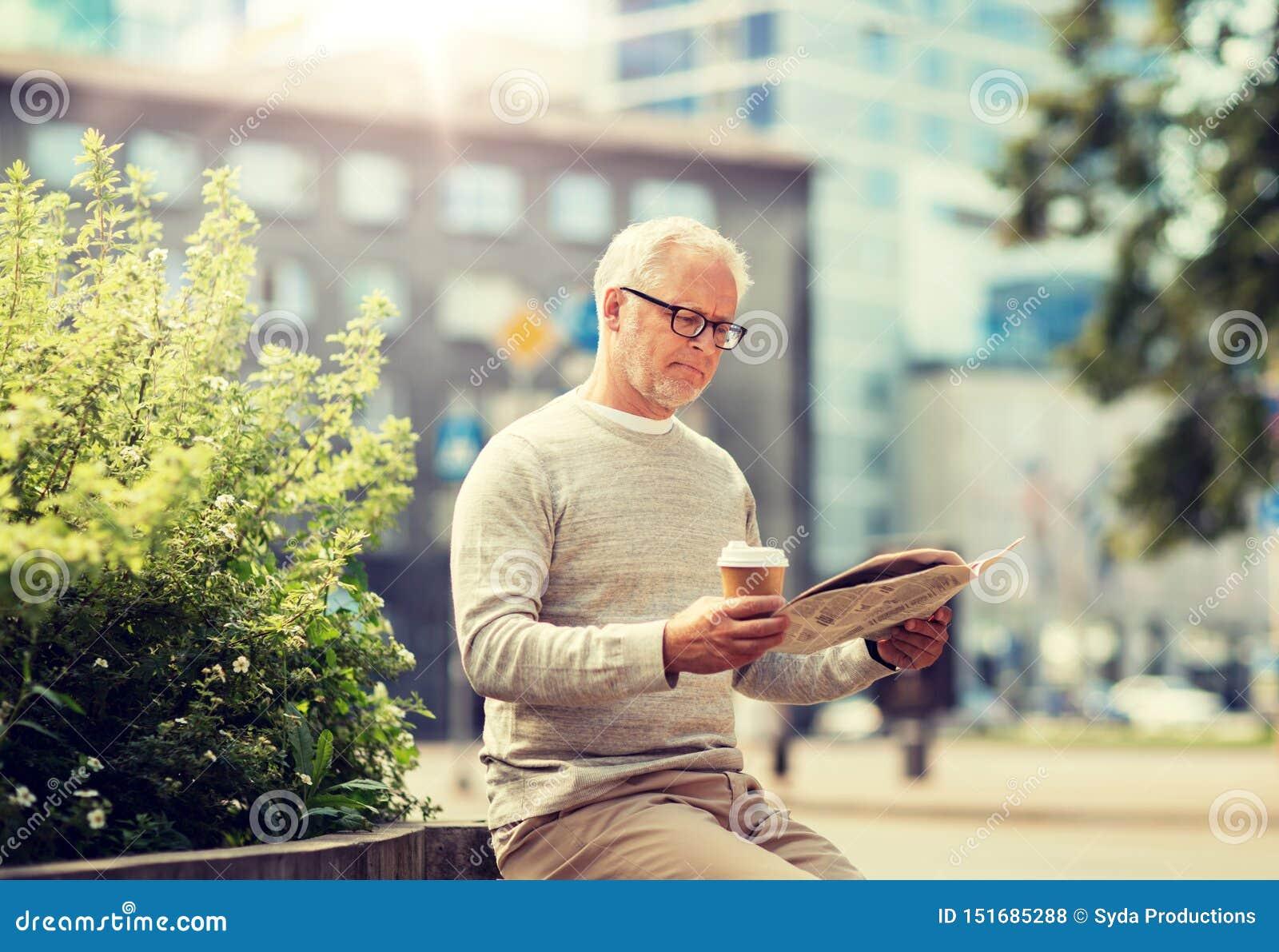 老人读书报纸和饮用的咖啡