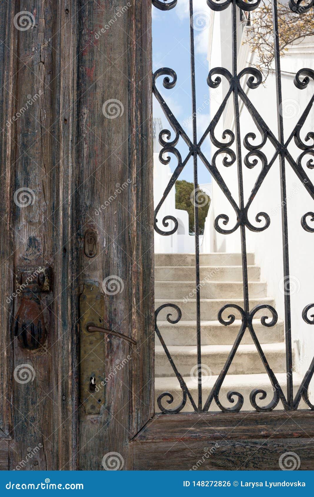 老以手的形式铁生锈的门把手 一个房子的布朗木门在Tira希腊,在海岛上