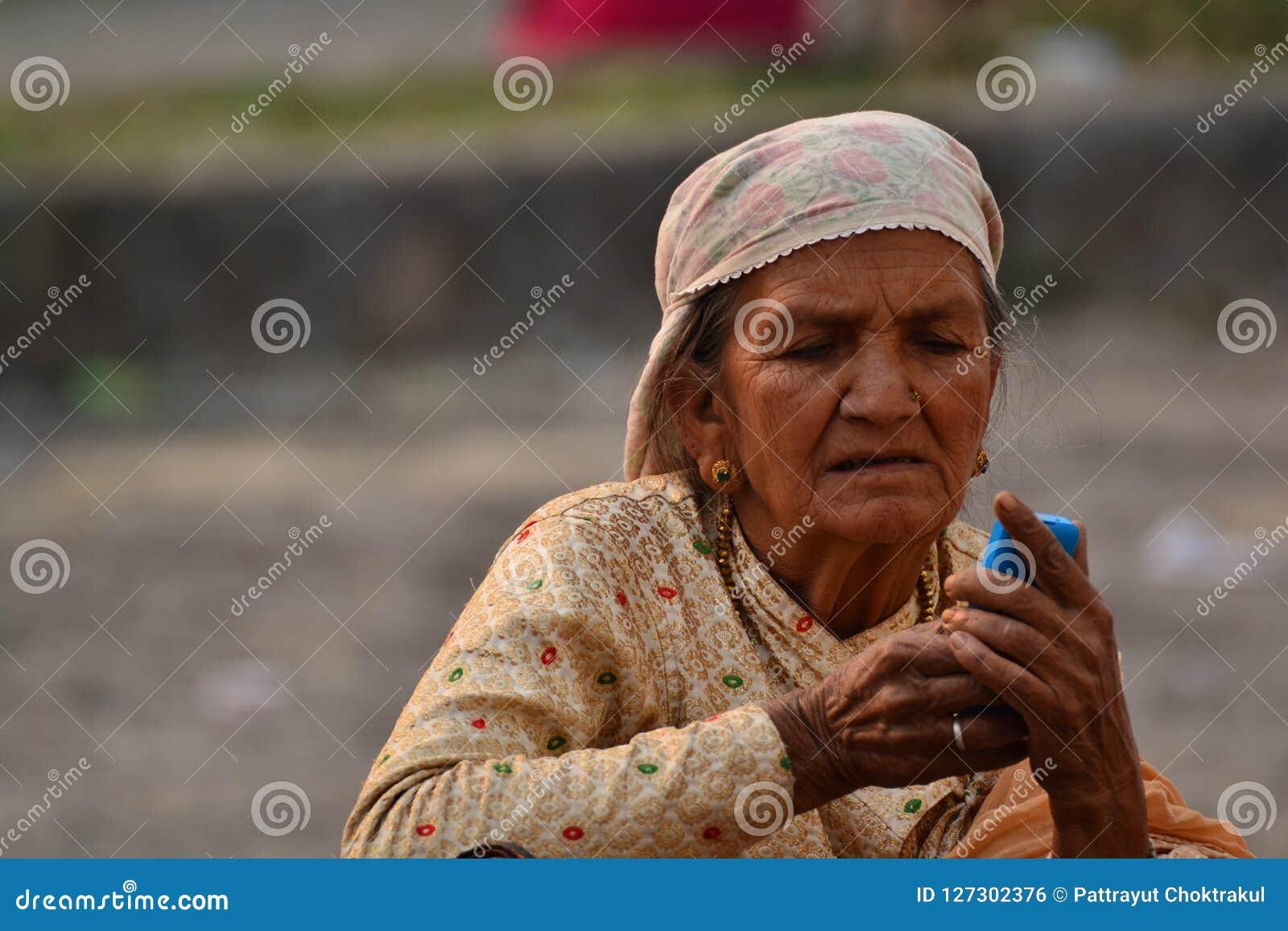 老妇人使用手机用两手