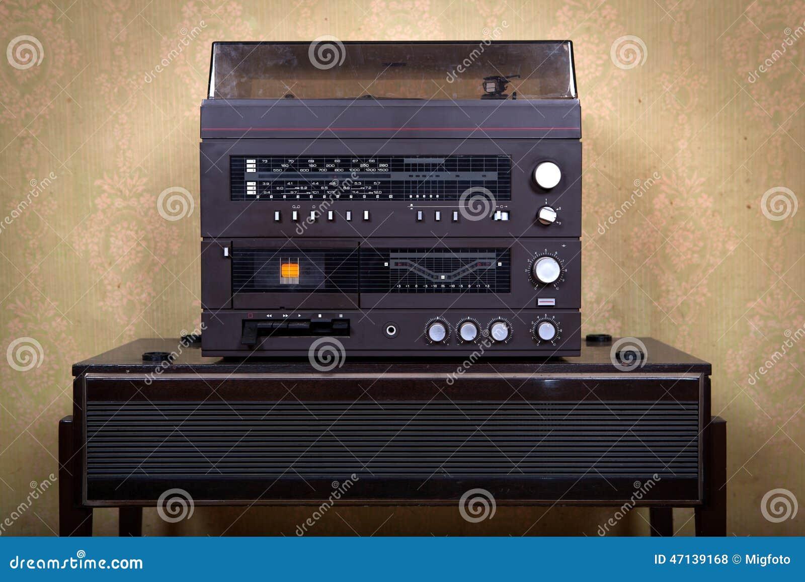 古色古香的褴褛收音机在与葡萄酒墙纸的老屋子内部里.图片
