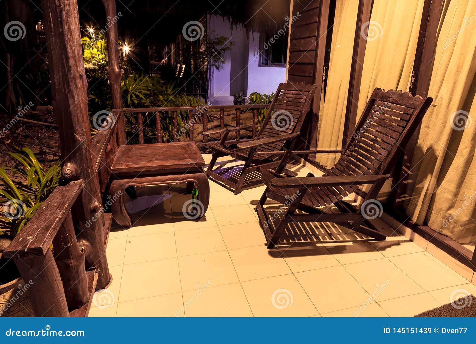 老木桌和木椅子,在平房房子的门廊的立场 在街道上在晚上