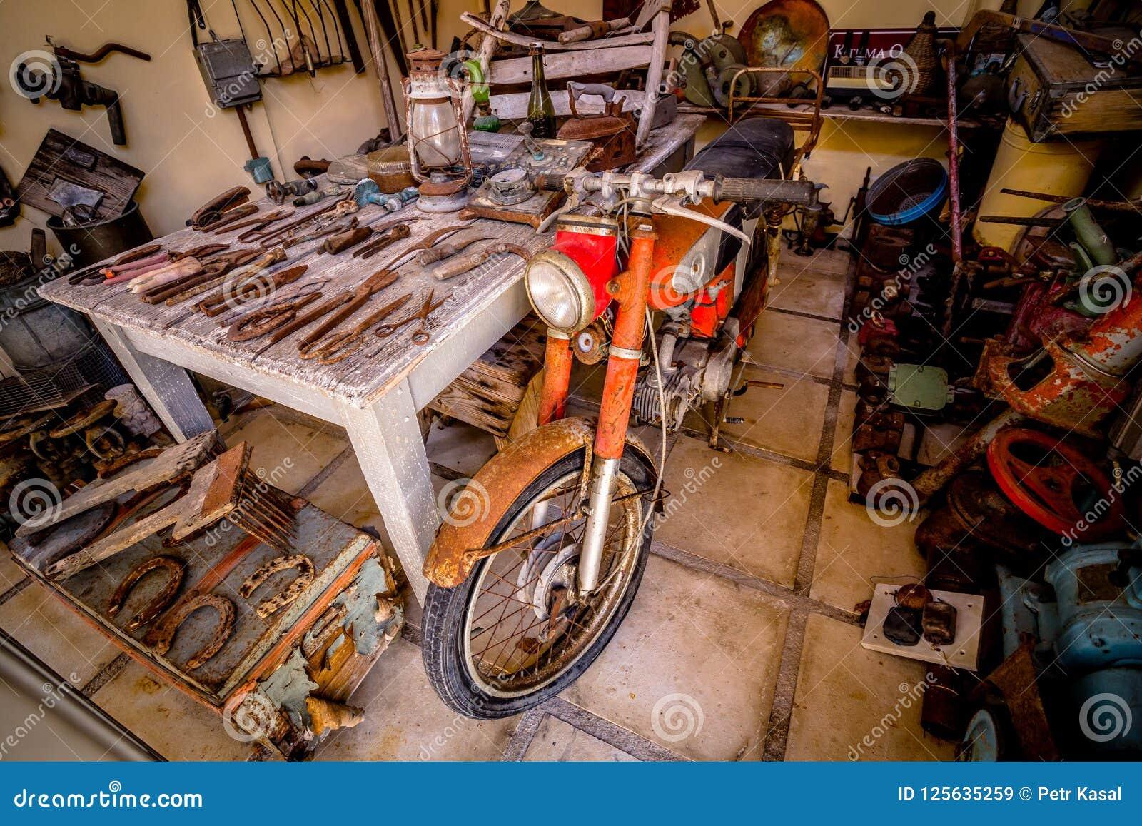 老生锈的摩托车在有老生锈的工具的棚子