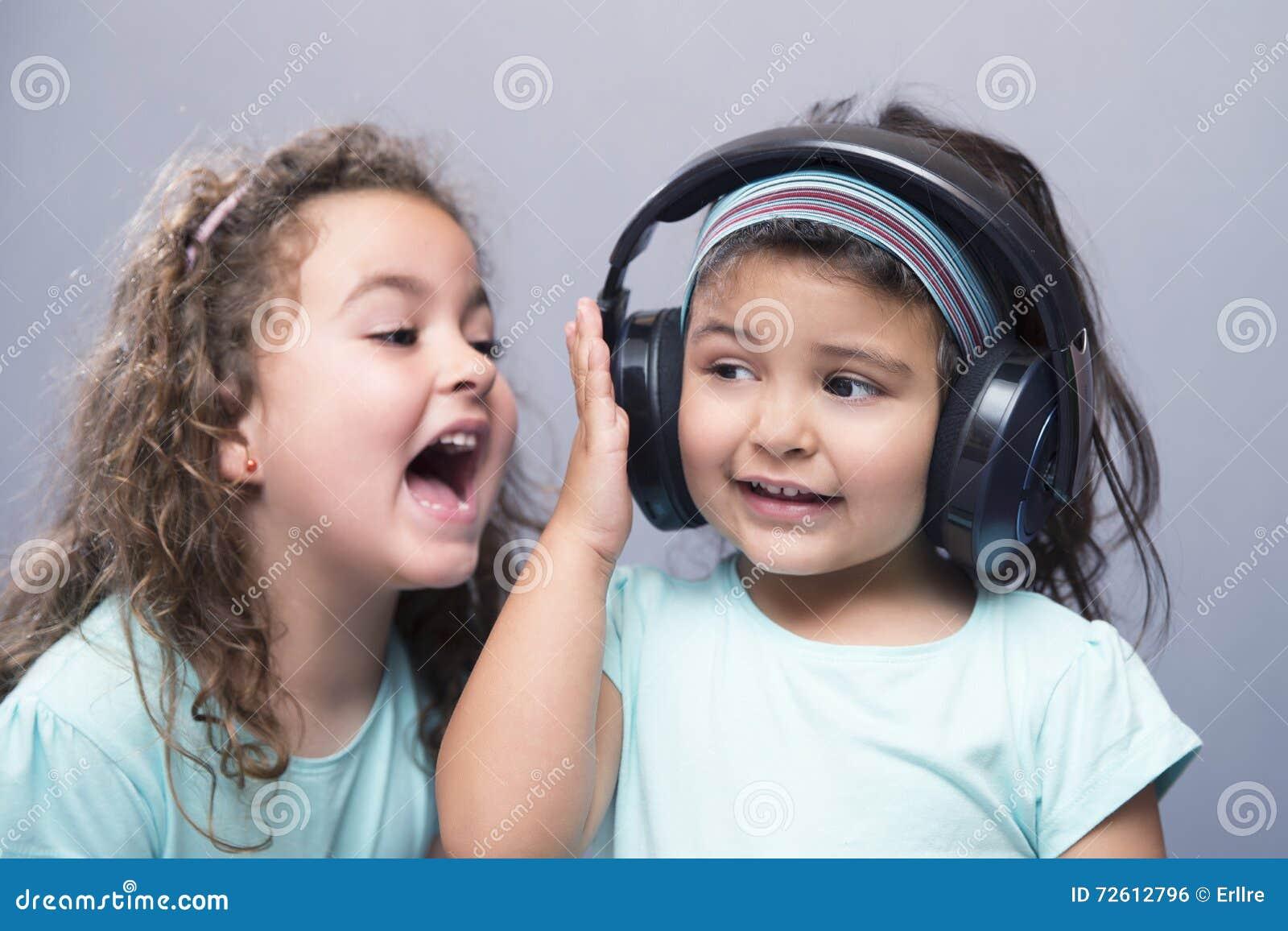 更老的姐妹尖叫对她的耳机的妹妹