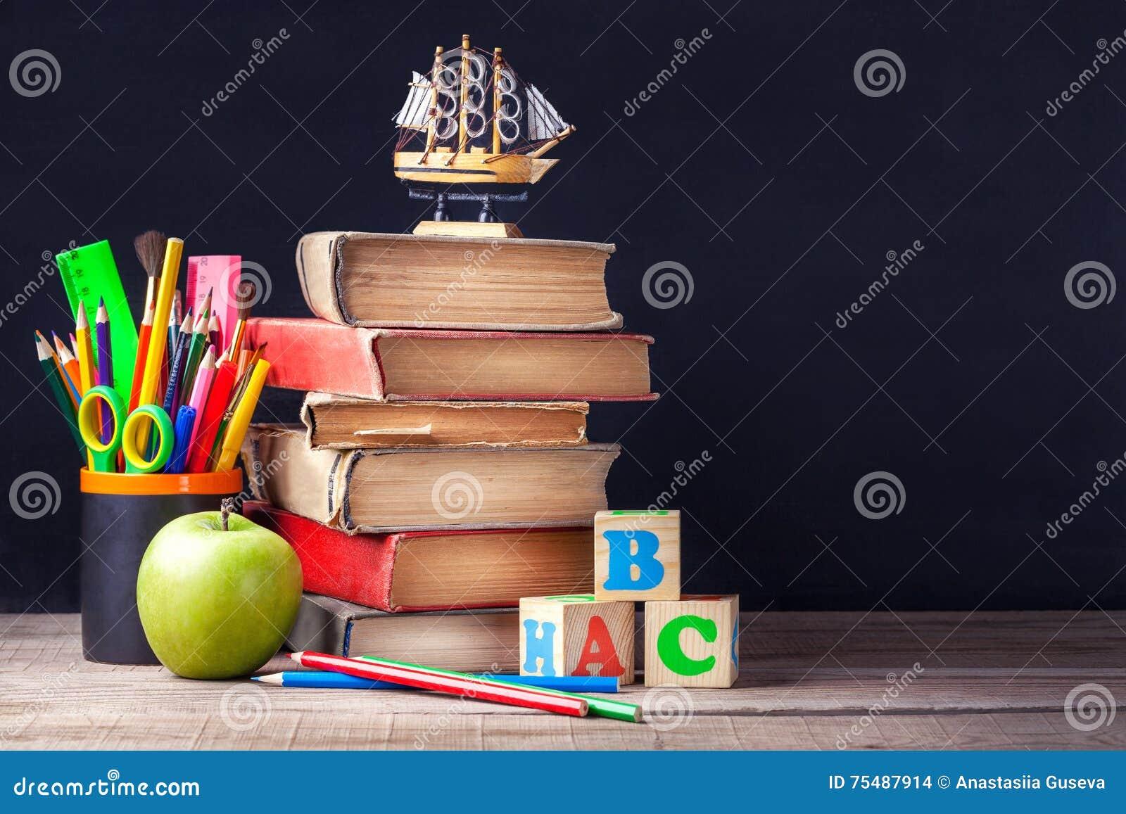 老课本和学校用品在黑粉笔板背景的土气木桌上