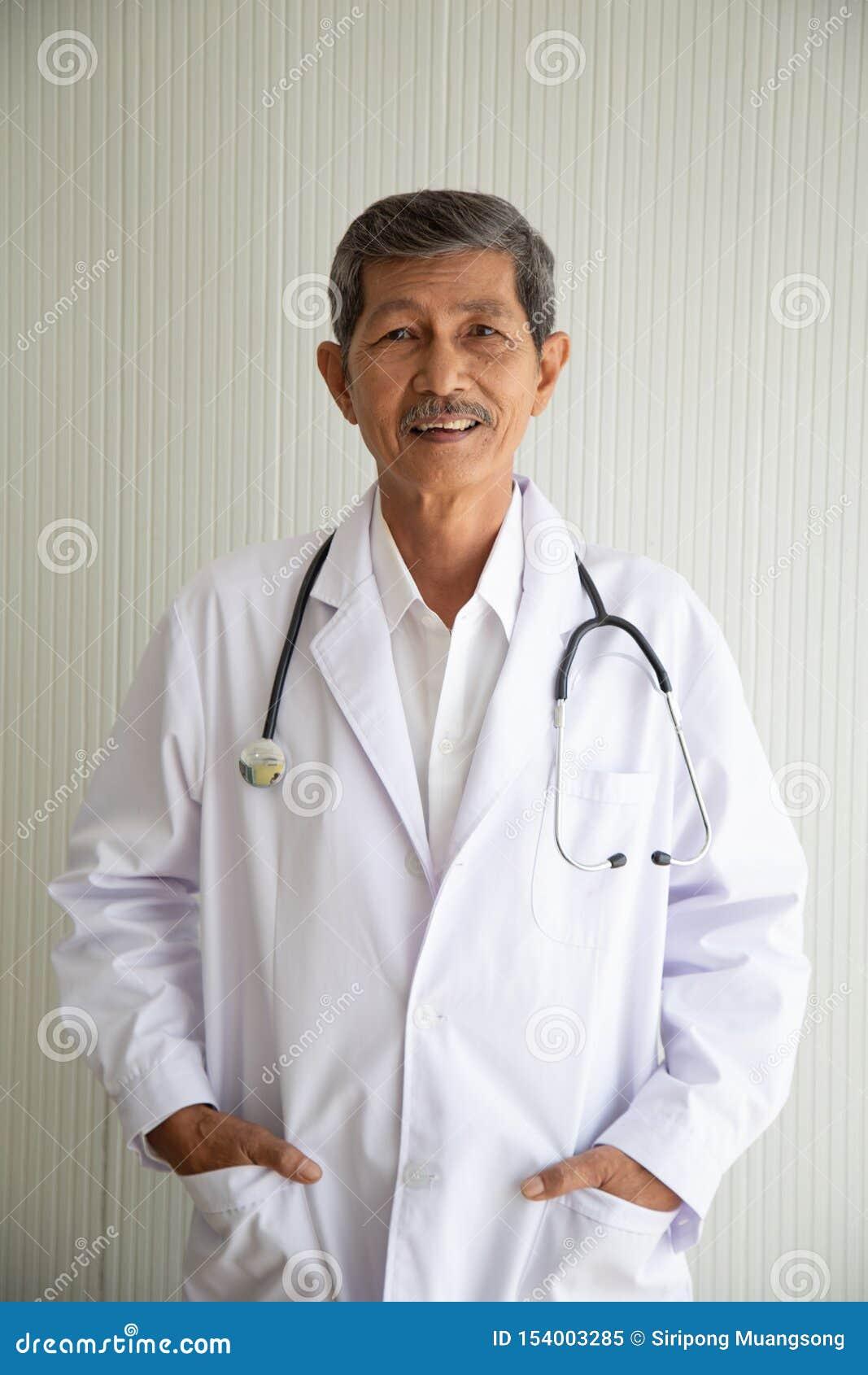 老资深亚洲医生微笑画象与制服的