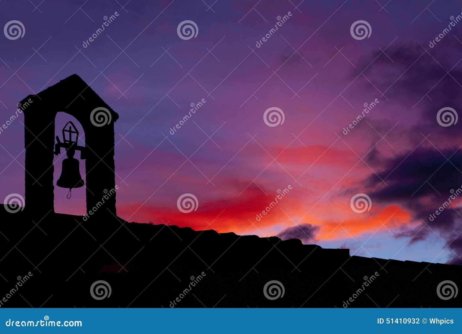 老钟楼剪影点燃了与最后光在日落, montanchez,西班牙.图片